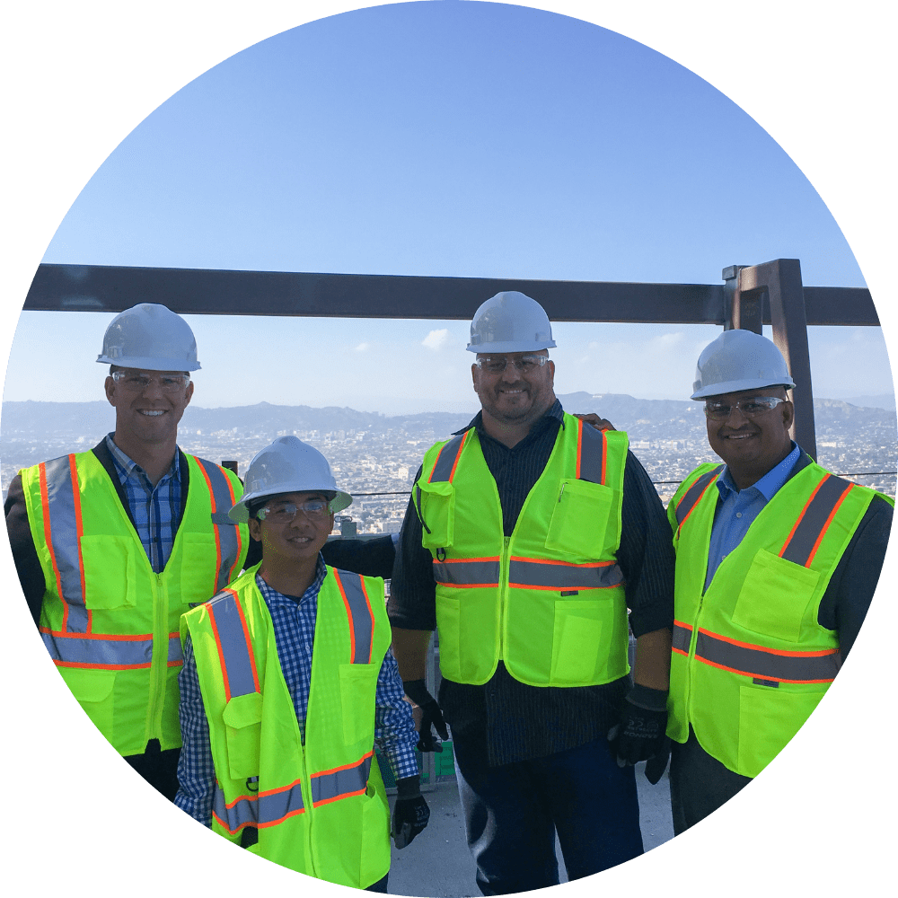 Group photo of men wearing construction vests and hard hats